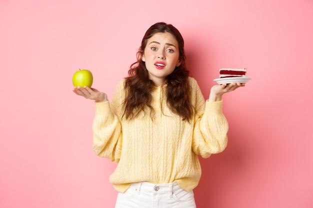 Niezdecydowana smutna młoda kobieta wzruszająca ramionami, trzymając zielone zdrowe jabłko i fast foody kawałek ciasta wyglądająca na zdezorientowaną i zdenerwowaną stojącą przed różową ścianą