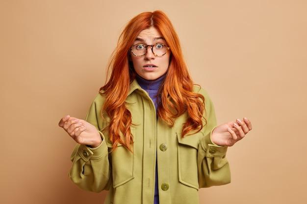 Niezdecydowana, zdezorientowana ruda kobieta rozkłada dłonie na boki i czuje zdezorientowane spojrzenia z zszokowaną miną, ubrana w modną odzież wierzchnią.