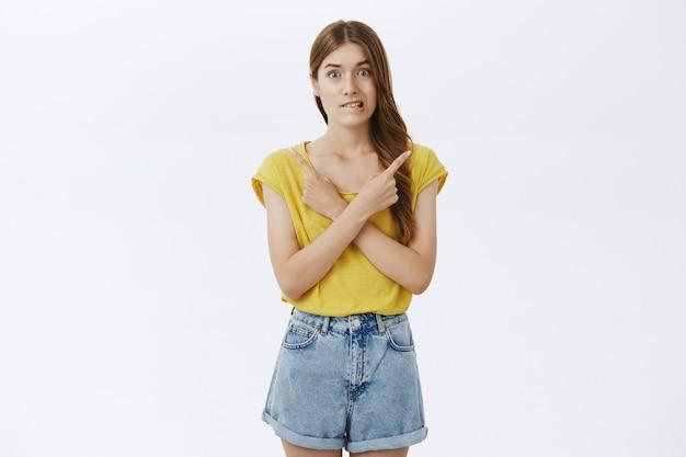 Niezdecydowana, zdziwiona śliczna dziewczyna wskazująca w bok i wskazująca dwa warianty, dokonując wyboru