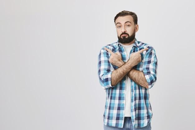 Niezdecydowany dorosły mężczyzna brodaty klient wskazując bokiem