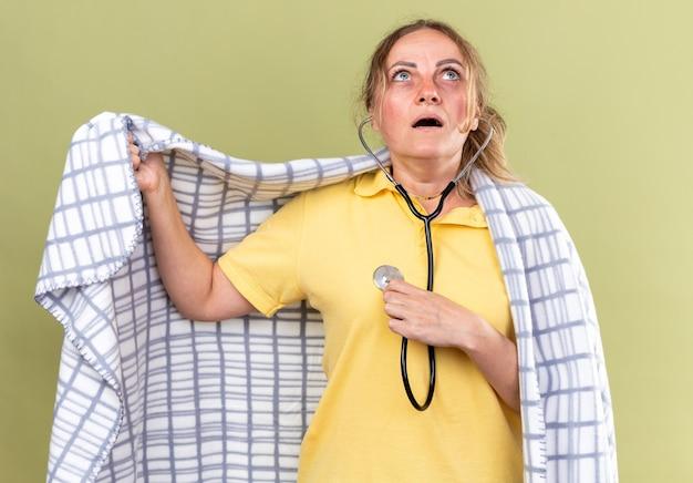 Niezdrowa kobieta owinięta w koc źle się czuje, cierpi na grypę i przeziębienie, słuchając bicia serca za pomocą stetoskopu, patrząc zmartwioną, stojąc nad zieloną ścianą