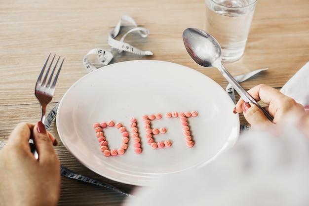 Niezdrowa kobieta ręka mówi pigułki diety