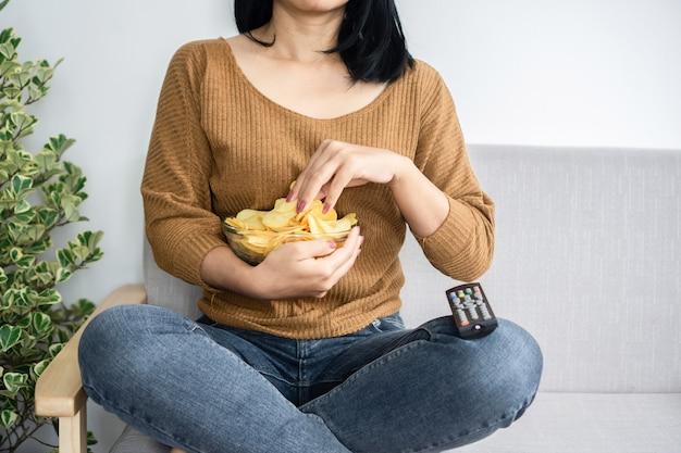 Niezdrowa kobieta siedzi na kanapie jedzenie chipsów ziemniaczanych