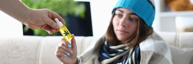 Niezdrowa kobieta używa oleju cbd