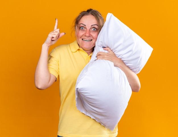 Niezdrowa kobieta w żółtej koszuli, cierpiąca na grypę i przeziębienie, przytula poduszkę pokazującą indeks fignera pokazujący indeks fignera uśmiechający się, lepiej stojący nad pomarańczową ścianą