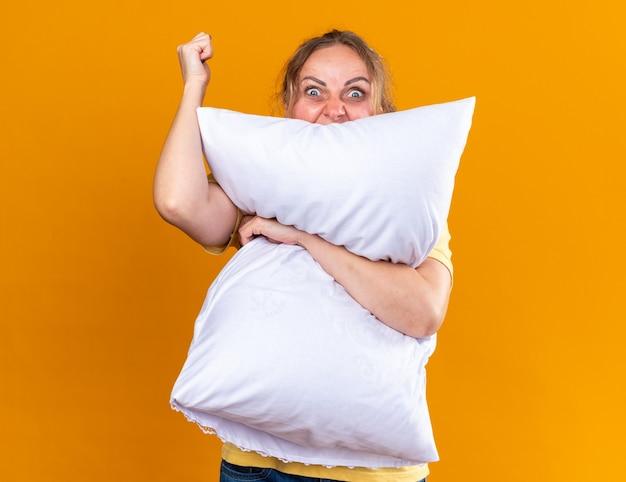 Niezdrowa kobieta w żółtej koszuli, cierpiąca na grypę i zimno, źle się czuje, przytula poduszkę z gniewną twarzą unoszącą pięść stojącą nad pomarańczową ścianą
