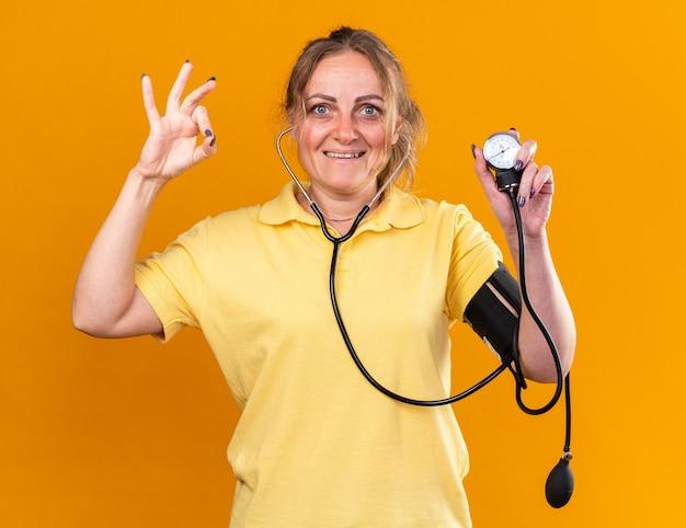 Niezdrowa kobieta w żółtej koszuli czuje się lepiej mierząc ciśnienie krwi za pomocą tonometru uśmiechając się pokazując znak ok stojący nad pomarańczową ścianą