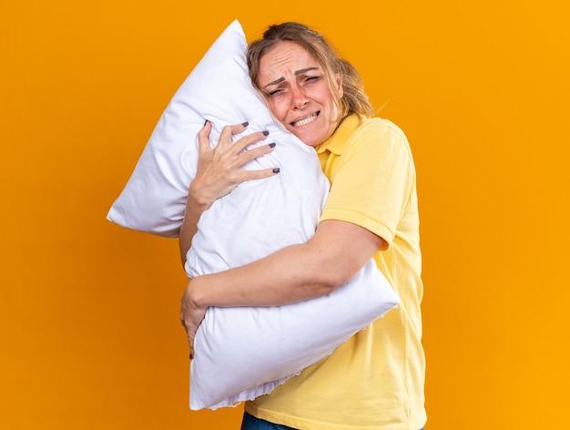 Niezdrowa kobieta w żółtej koszuli źle się czuje, cierpi na grypę i zimną poduszkę do przytulania, cierpi na gorączkę stojącą nad pomarańczową ścianą