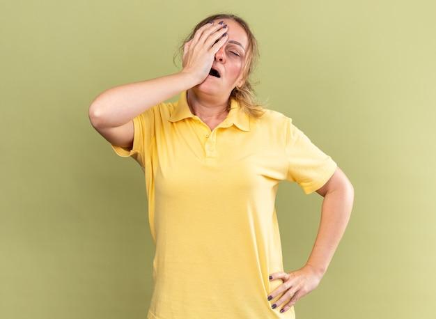 Niezdrowa kobieta w żółtej koszuli źle się czuje dotykając czoła, mając zawroty głowy z grypą stojącą nad zieloną ścianą