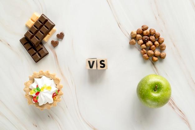 Niezdrowa kremowa tarta; czekolada vs zdrowy orzech laskowy; jabłko na tle tekstury