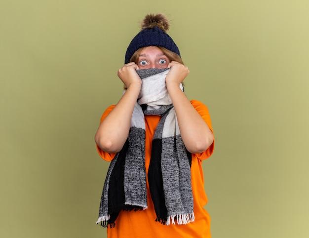 Niezdrowa młoda kobieta nosząca kapelusz z szalikiem na szyi, źle się czuje, wygląda na przestraszoną, cierpi z powodu wirusa stojącego nad zieloną ścianą