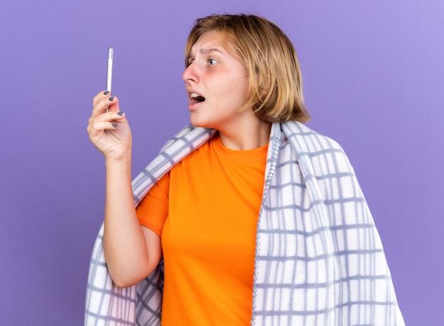 Niezdrowa młoda kobieta owinięta ciepłym kocem czuje się chora, cierpi na grypę, ma gorączkę i mierzy jej temperaturę za pomocą termometru, patrząc zmartwioną, stojąc nad fioletową ścianą