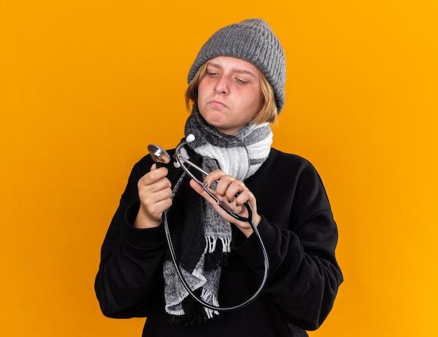 Niezdrowa młoda kobieta w ciepłym kapeluszu i szaliku na szyi, chora na przeziębienie i grypę, trzymająca stetoskop, patrząca na niego z poważną miną