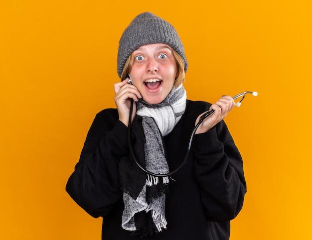 Niezdrowa młoda kobieta w ciepłym kapeluszu i szaliku na szyi, cierpiąca na przeziębienie i grypę ze stetoskopem, czuje się lepiej, uśmiechając się, stojąc nad pomarańczową ścianą