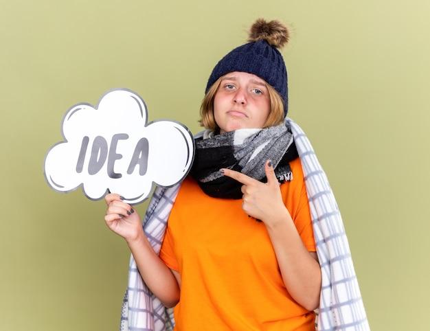 Niezdrowa młoda kobieta w ciepłym kapeluszu i szaliku na szyi owinięta w koc, czując się źle złapana przeziębieniem, trzymająca znak dymka z pomysłem na słowo wskazującym palcem