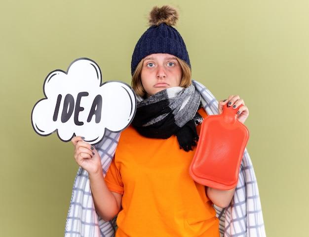 Niezdrowa młoda kobieta w ciepłym kapeluszu i szaliku na szyi owinięta w koc źle się czuje złapana przeziębieniem trzymając butelkę z gorącą wodą i znak dymek z pomysłem na słowo