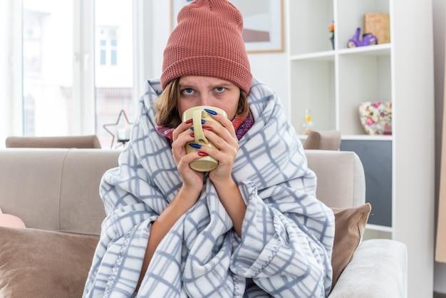 Niezdrowa młoda kobieta w kapeluszu owinięta w koc źle się czuje i choruje, cierpi na przeziębienie i grypę, pije gorącą herbatę, aby wyzdrowieć, siedząc na kanapie w jasnym salonie