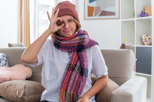 Niezdrowa młoda kobieta w kapeluszu z ciepłym szalikiem na szyi, cierpiąca na przeziębienie i grypę, czuje się lepiej, robiąc znak ok, uśmiechając się, siedząc na kanapie w jasnym salonie