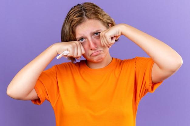 Niezdrowa młoda kobieta w pomarańczowym t-shircie czuje się okropnie trzymająca tkankę cierpiącą na katar, kaszląca na zimno, płacząca mocno pocierająca oczy stojąca nad fioletową ścianą