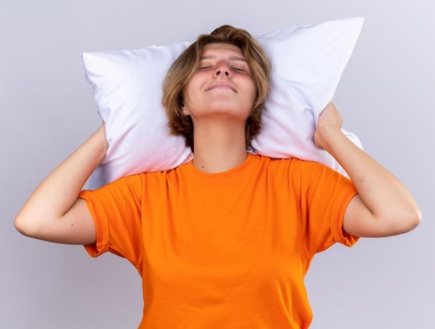 Niezdrowa młoda kobieta w pomarańczowym t-shircie trzymająca poduszkę, która lepiej się uśmiecha z zamkniętymi oczami, stojąc nad białą ścianą