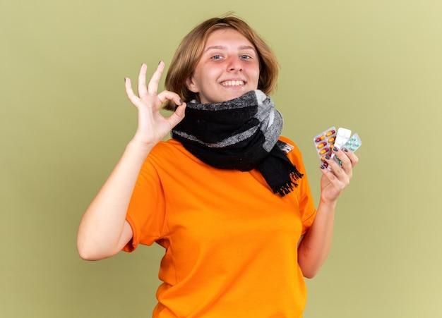 Niezdrowa młoda kobieta w pomarańczowym t-shircie z ciepłym szalikiem na szyi czuje się lepiej trzymając różne pigułki uśmiechając się pokazując znak ok