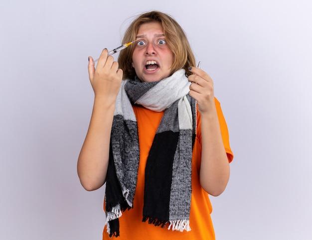 Niezdrowa młoda kobieta w pomarańczowym t-shircie z ciepłym szalikiem na szyi, strasznie cierpiąca na grypę, trzymająca strzykawkę i ampułkę, wyglądająca na zmartwioną i przestraszoną, zdezorientowaną, stojąc nad białą ścianą