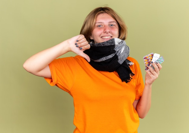 Niezdrowa młoda kobieta w pomarańczowym t-shircie z ciepłym szalikiem wokół szyi, lepiej trzymająca różne pigułki, uśmiechająca się pokazując kciuk w dół stojący nad zieloną ścianą