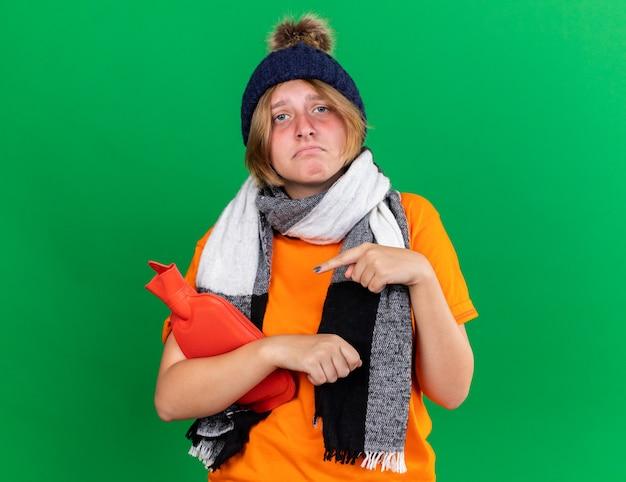 Niezdrowa młoda kobieta w pomarańczowym t-shircie z czapką i ciepłym szalikiem na szyi, czuje się okropnie trzymając termofor i cierpi na zimno