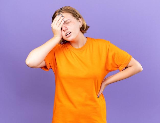 Niezdrowa młoda kobieta w pomarańczowym t-shircie źle się czuje dotykając czoła, mając zawroty głowy z grypą stojącą nad fioletową ścianą