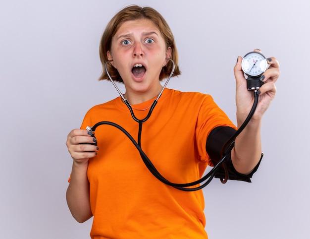 Niezdrowa młoda kobieta w pomarańczowym t-shircie źle się czuje, mierząc ciśnienie krwi za pomocą tonometru, patrząc zmartwioną i przestraszoną, stojąc nad białą ścianą