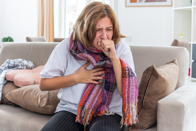 Niezdrowa młoda kobieta z ciepłym szalikiem na szyi czuje się okropnie cierpi na kaszel wirusa, siedząc na kanapie w jasnym salonie