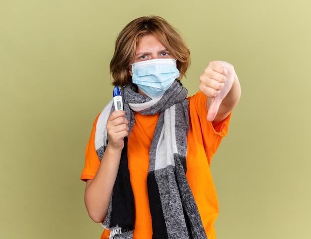 Niezdrowa młoda kobieta z ciepłym szalikiem na szyi, ubrana w ochronną maskę na twarz, trzymającą termometr, źle się czuje pokazując kciuk w dół