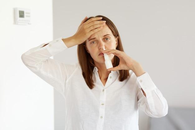 Niezdrowa, ujmująca kobieta o przyjemnym wyglądzie, ubrana w białą koszulę w stylu casual, używająca sprayu do nosa na katar, czuje grypę, przeziębienie, ból głowy.