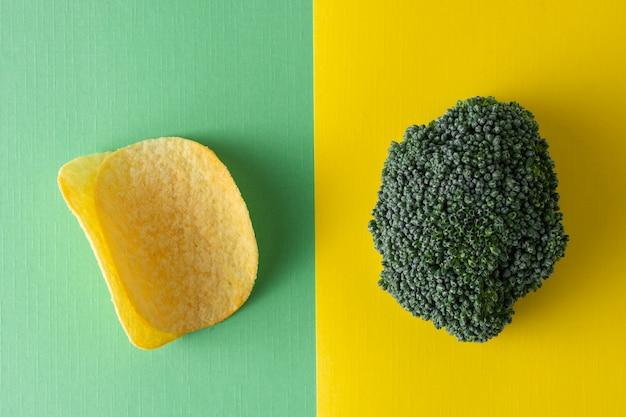 Niezdrowe a zdrowe jedzenie. wybierz chipsy ziemniaczane lub brokuły. widok z góry, kolorowy.