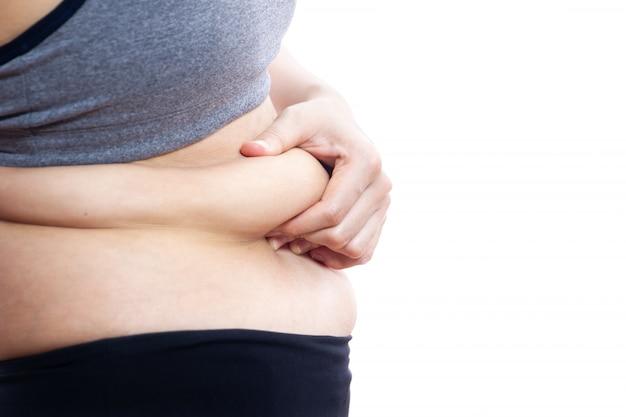 Niezdrowe grube kobiety łapiące na brzuchu z bliska. samodzielnie na białym tle.