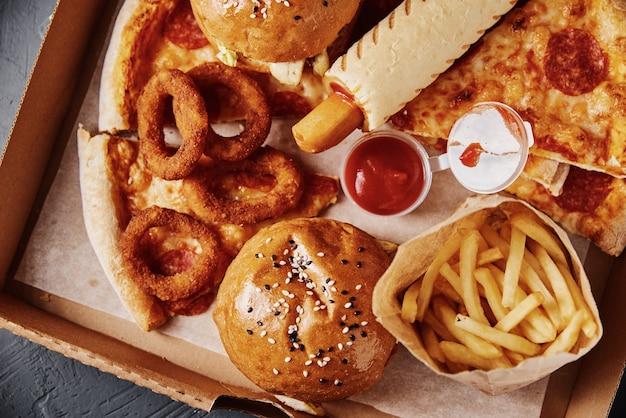 Niezdrowe i niezdrowe jedzenie. różne rodzaje fast foodów na stole, z bliska