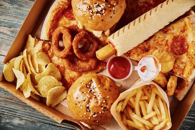 Niezdrowe i niezdrowe jedzenie. różne rodzaje fast foodów na stole