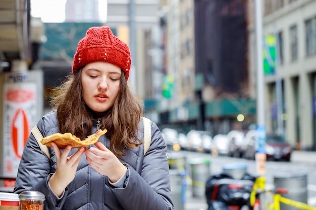 Niezdrowe jedzenie i jedzenie uliczne dziewczyna ładna nastolatka, z cute, z kawałka pysznej pizzy