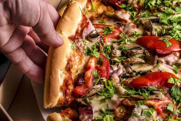 Niezdrowe jedzenie, kalorie. domowa pizza ze świeżym szynkowym szynką grzybową. czas pizzy. ręką człowieka biorąc plastry pizzy lub pudełko