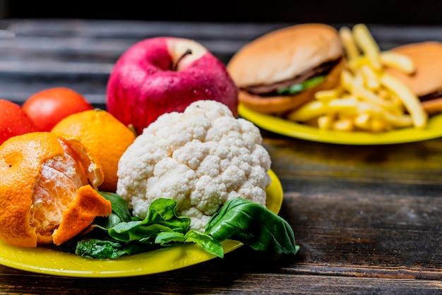 Niezdrowe jedzenie lub zdrowe warzywa i owoce na ciemnym drewnianym stole na białym tle b