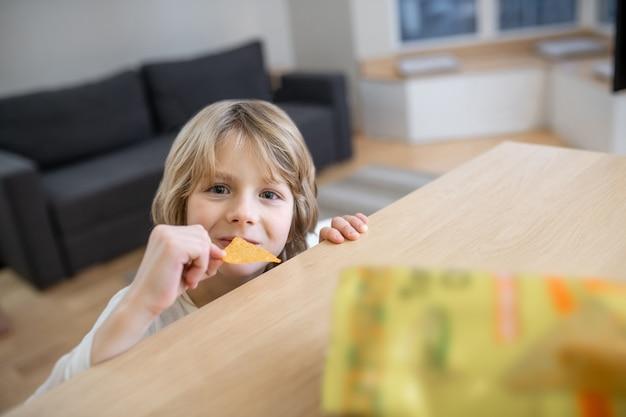Niezdrowe jedzenie. zbliżenie na słodkiego chłopca jedzącego chipsy ziemniaczane