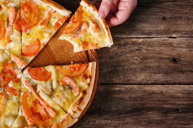Niezdrowe jedzenie, złe nawyki, niezdrowe jedzenie. osoba nie do poznania bierze ugryziony kawałek pizzy serwowane na tle ciemnego drewnianego stołu.