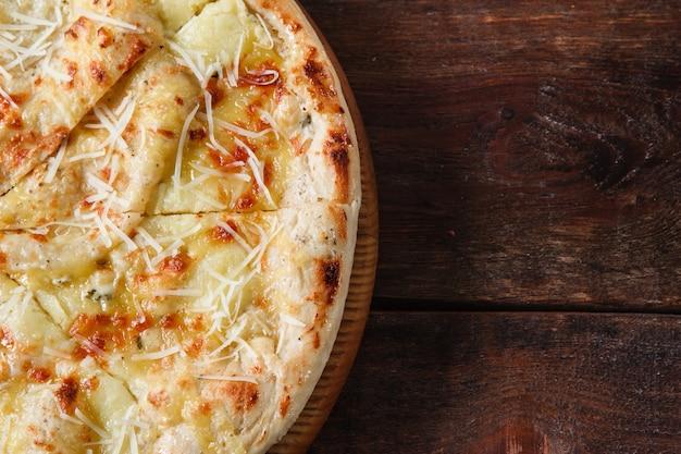 Niezdrowe jedzenie, złe nawyki, niezdrowe odżywianie, kalorie. świeża pizza z gorącym serem podawana na rustykalnym drewnianym stole, płasko leżąca z wolnym miejscem na tekst.