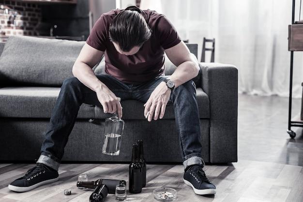 Niezdrowe uzależnienie. smutny przygnębiony pijany mężczyzna siedzi na kanapie i trzyma butelkę wódki podczas picia