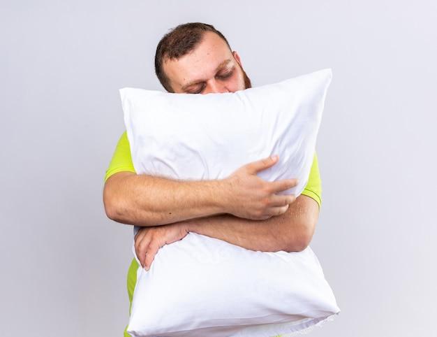 Niezdrowy brodaty mężczyzna w żółtej koszulce polo czuje się chory przytulając poduszkę chce spać z zamkniętymi oczami, stojąc nad białą ścianą