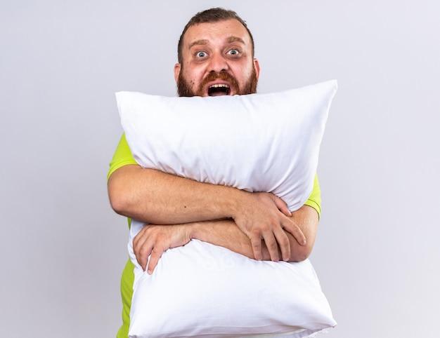 Niezdrowy brodaty mężczyzna w żółtej koszulce polo czuje się chory przytulając poduszkę krzycząc z zirytowanym wyrazem twarzy stojąc nad białą ścianą