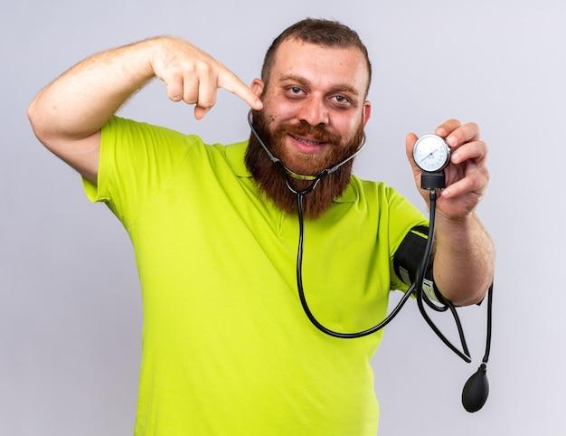 Niezdrowy brodaty mężczyzna w żółtej koszulce polo czuje się lepiej mierząc ciśnienie krwi za pomocą tonometru wskazującego palcem wskazującym, uśmiechając się stojąc nad białą ścianą
