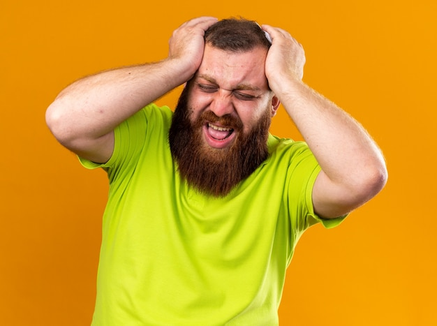 Niezdrowy brodaty mężczyzna w żółtej koszulce polo czuje się okropnie cierpiąc z powodu zimna i silnego bólu głowy dotykającego jego głowy