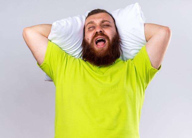 Niezdrowy brodaty mężczyzna w żółtej koszulce polo z poduszką krzyczącą ze zirytowanym wyrazem twarzy stojącym nad białą ścianą