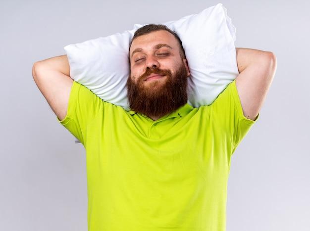Niezdrowy brodaty mężczyzna w żółtej koszulce polo z poduszką uśmiechający się szczęśliwy i pozytywny z zamkniętymi oczami na białej ścianie